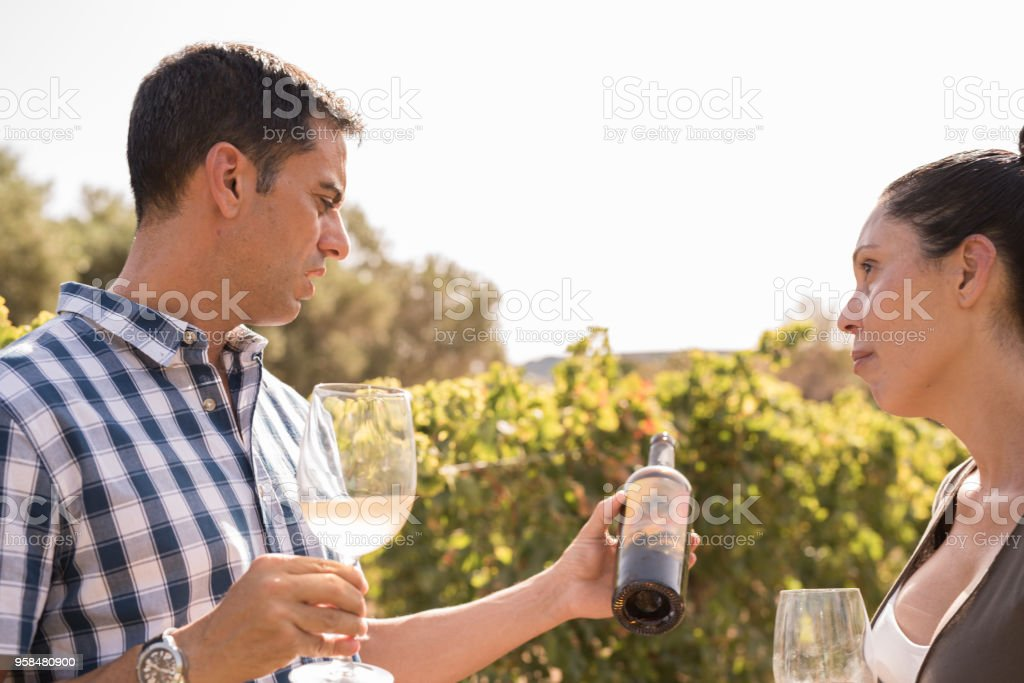 A man and woman talking over a bottle of wine stock photo