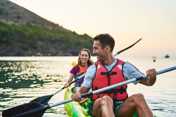 Man and woman talking while kayaking on river stock photo