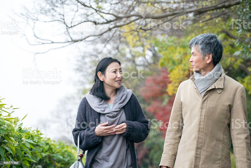 Man and woman talking while walking stock photo