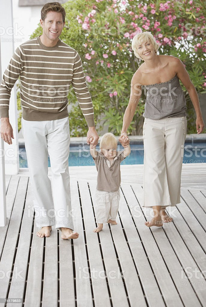 Man and woman teaching boy to walk royalty-free stock photo