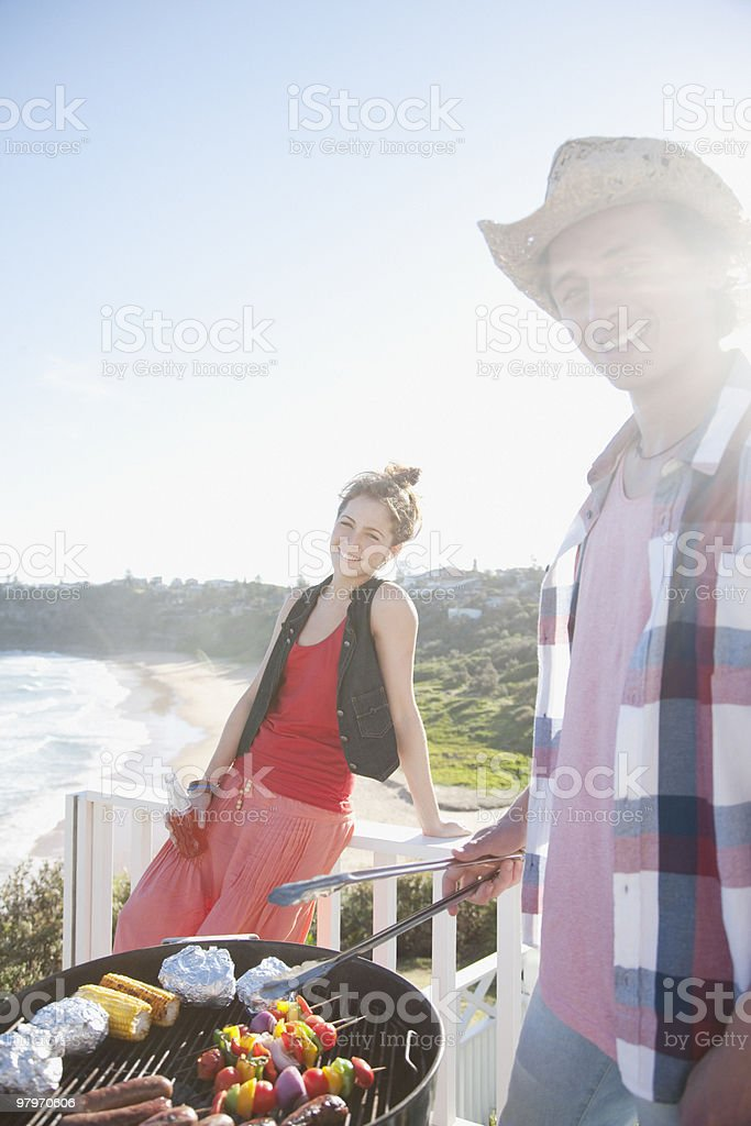 Man and woman tending barbecue with ocean in background royalty-free stock photo