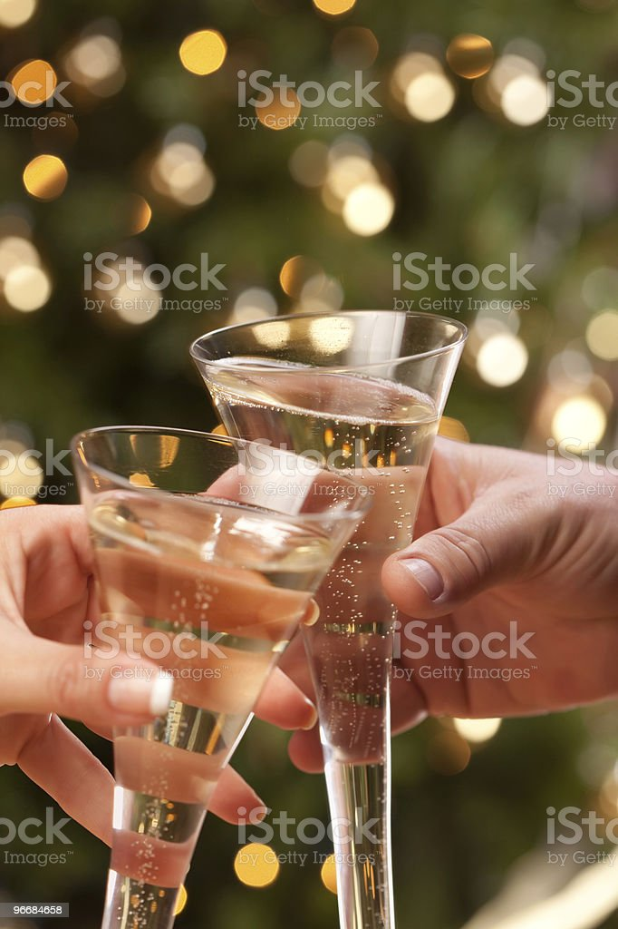 Man and Woman Toasting Champagne in Front of Lights royalty-free stock photo