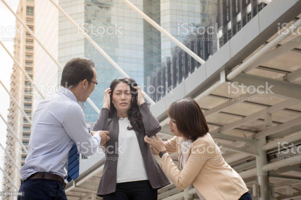 Man and woman try to help her friend who having a feeling faint on a sunny day stock photo