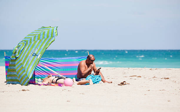 Man and woman under a big umbrella on the beach stock photo