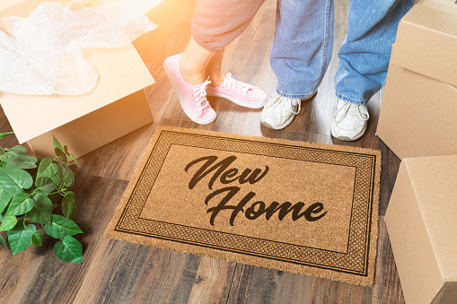 istock Man and Woman Unpacking Near New Home Welcome Mat, Moving Boxes and Plant 1164609452