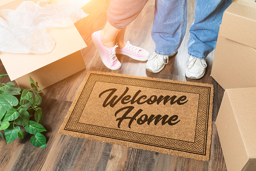 istock Man and Woman Unpacking Near Welcome Home Welcome Mat, Moving Boxes and Plant 1164609492