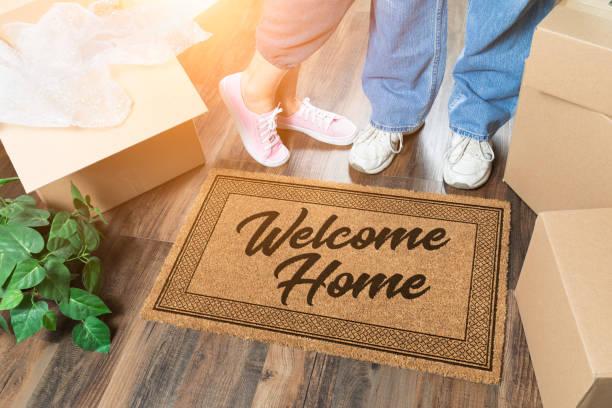 Mann und Frau Auspacken in der Nähe von Willkommen zu Hause Willkommen Matte, Umzugskartons und Pflanze – Foto