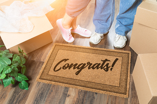 istock Man and Woman Unpacking Near Welcome Mat with Congrats, Moving Boxes and Plant 1164609506