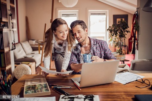 istock Man and woman using a laptop 621917242