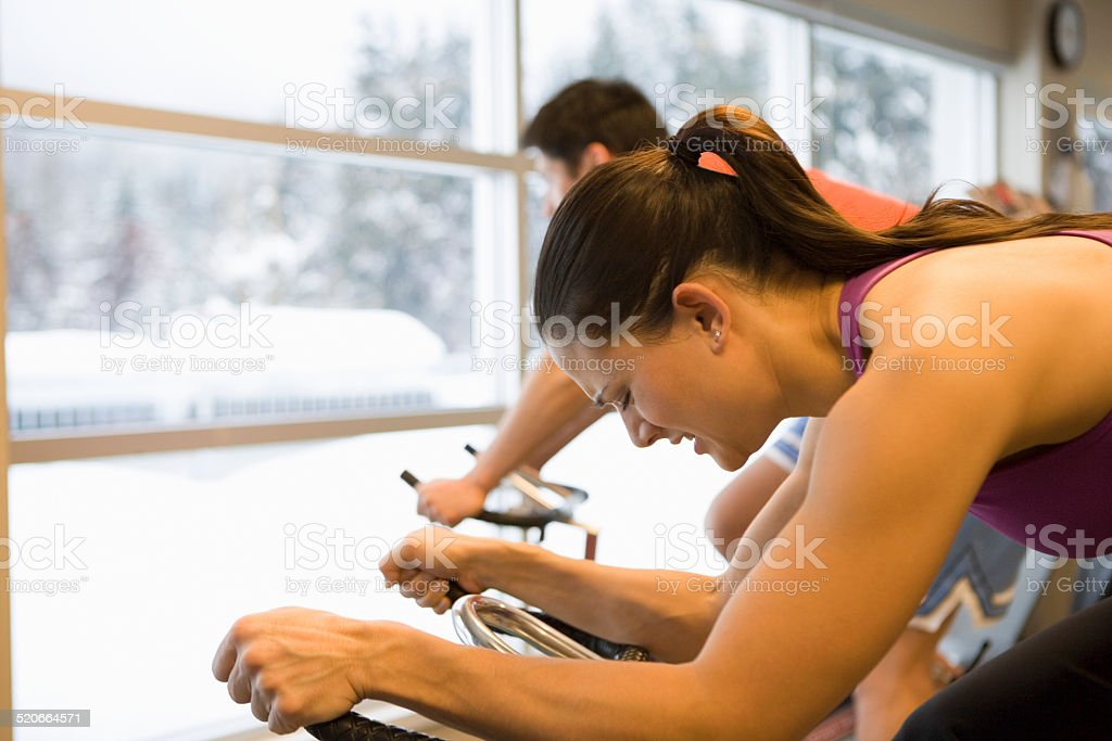Man and woman using exercise bikes in gym, side view stock photo