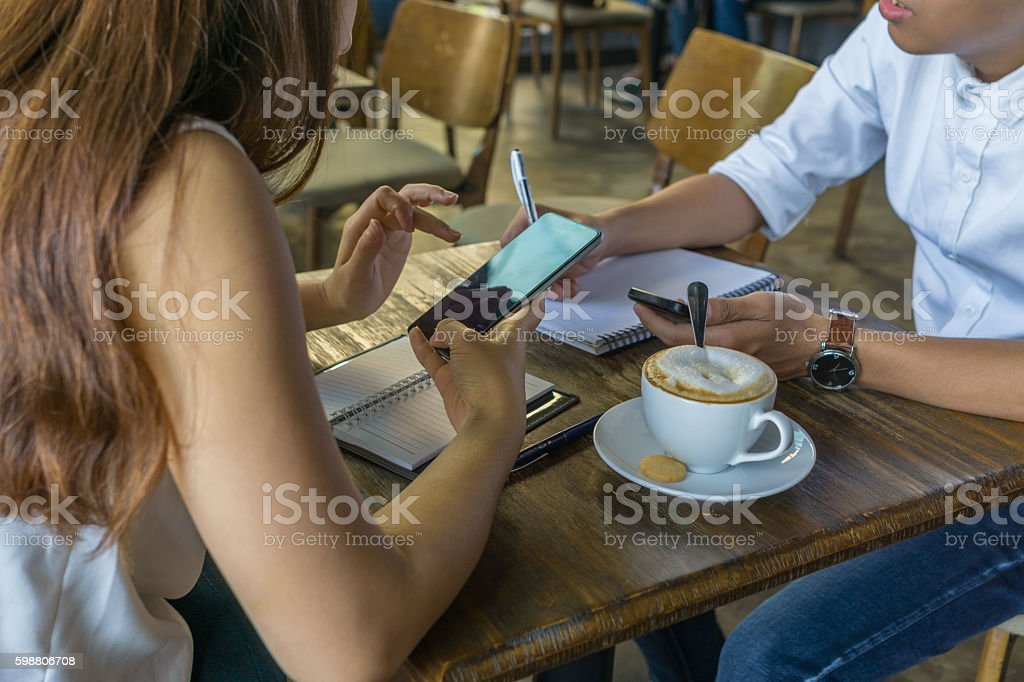 Man and woman using smartphone and having discussion in cafeteria stock photo