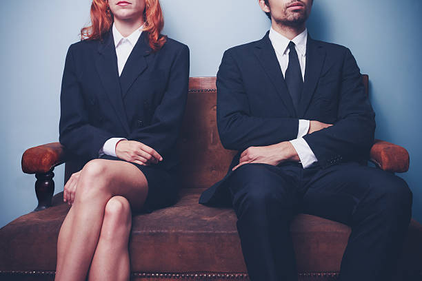 man and woman waiting on a sofa - gender stereotypes stock pictures, royalty-free photos & images
