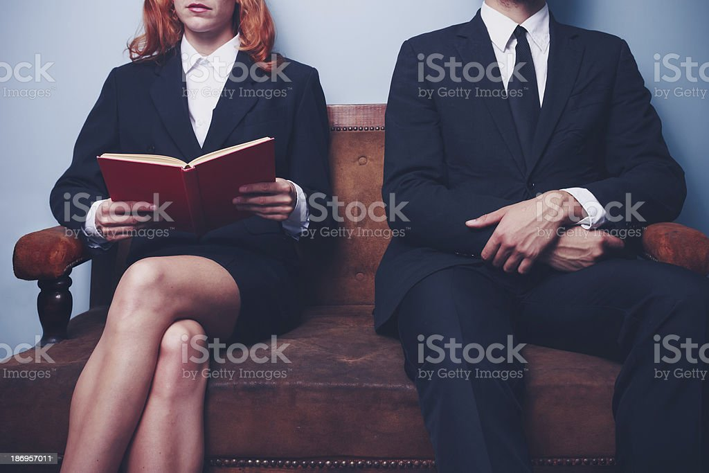 Man and woman waiting to enter a job interview stock photo