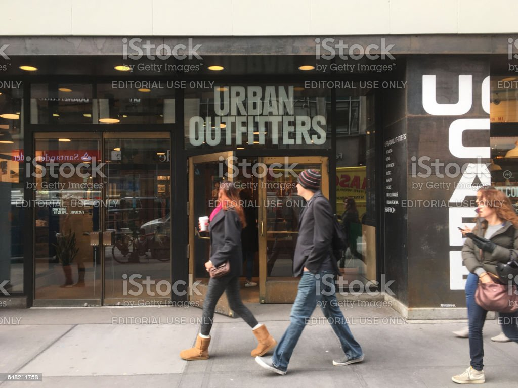 Man and woman walk passed Urban Outfitters retal store in Manhattan stock photo