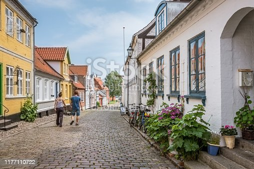 Man and woman walking along a picturesque lane with old houses and hollyhochs, The island of Aero, Denmark, July 13, 2019