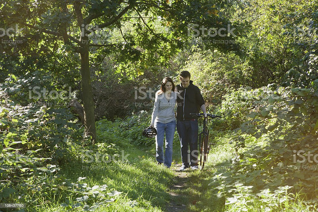 Man and woman walking in park stock photo