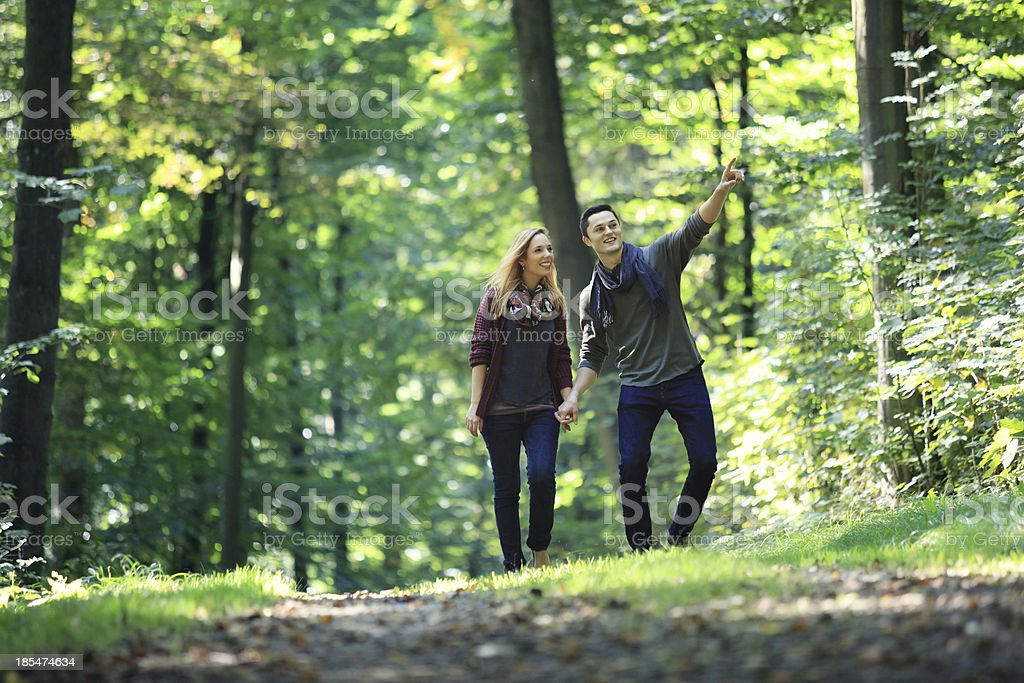 A man and woman walking in the forest stock photo