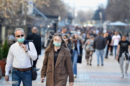 Sofia, Bulgaria - MAR 13 2020: A young woman and an older man are walking on Vitosha street. Few hours after that the Governemnt announced State of Emergency in the country because of the corona virus outbreak.