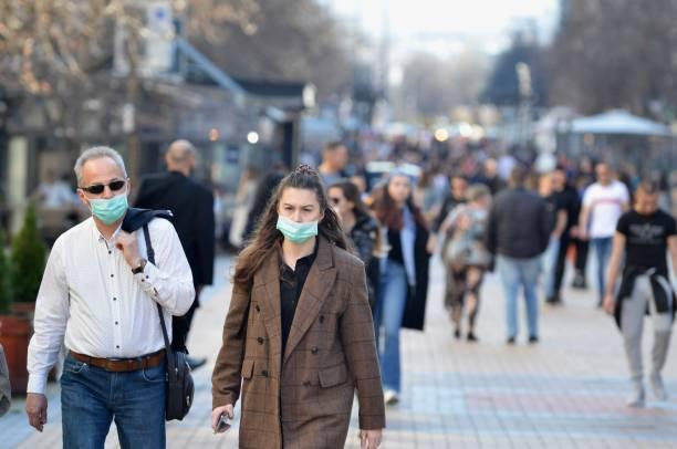 man och kvinna går i stadens centrum bär skyddsmasker - gata bildbanksfoton och bilder
