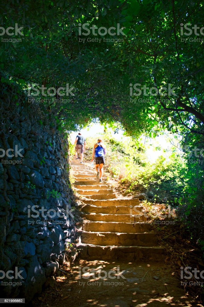 Man And Woman Walking Up Old Steps On Trail Linking Towns Of Cinque Terre - foto stock
