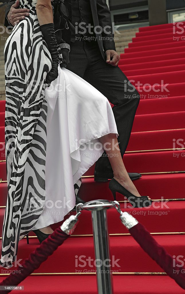 A man and woman walking up stairs on the red carpet stock photo