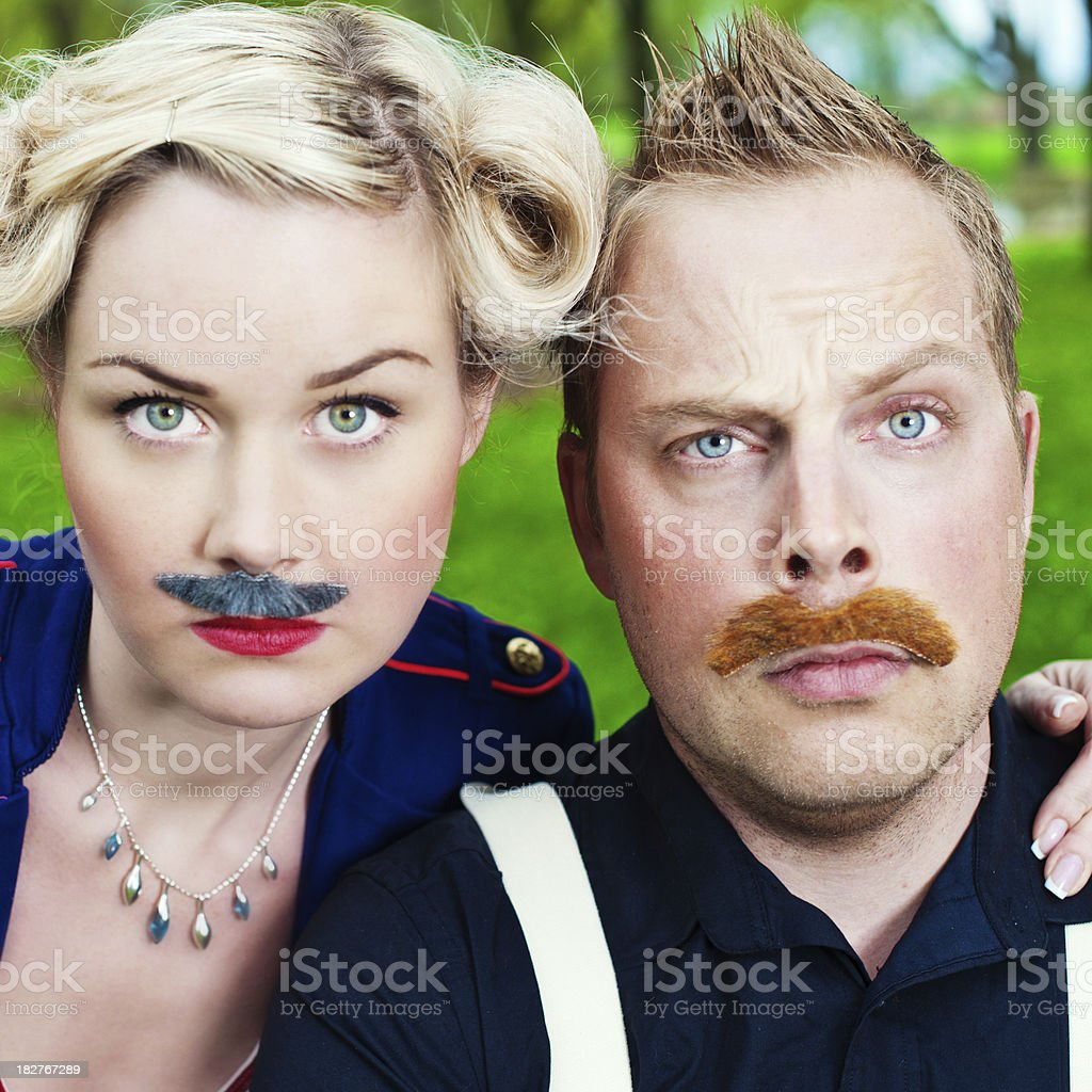 Man and woman wearing fake mustaches stock photo