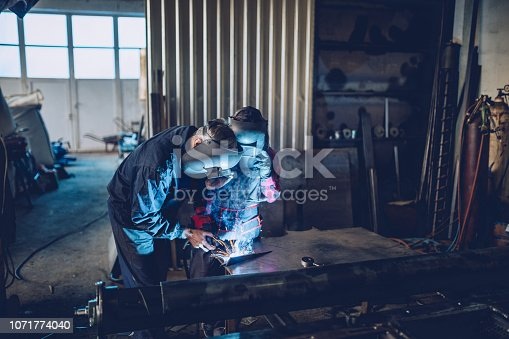 Man and woman welding together in workshop