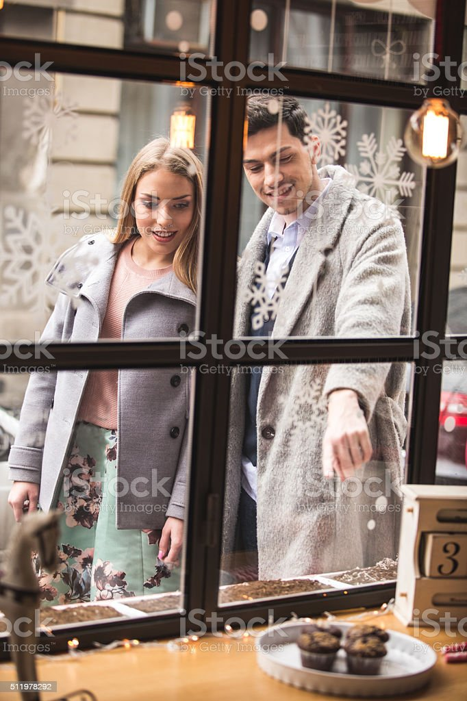Man and woman window shopping for cupcakes stock photo