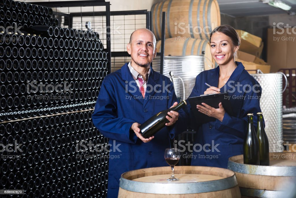 man and woman winemakers in wine cellar stock photo
