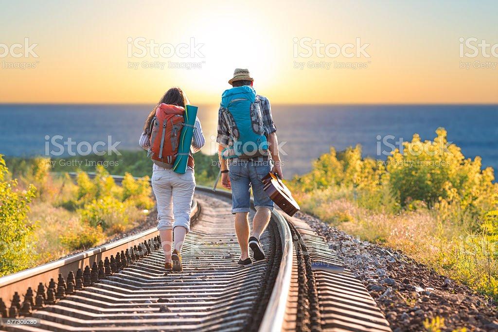 Man and Woman with Backpacks and Guitar walking toward Sea stock photo