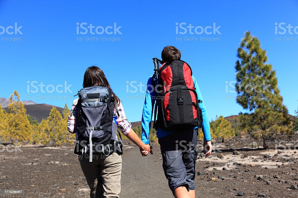 Man and woman with backpacks holding hands and hiking royalty-free stock photo