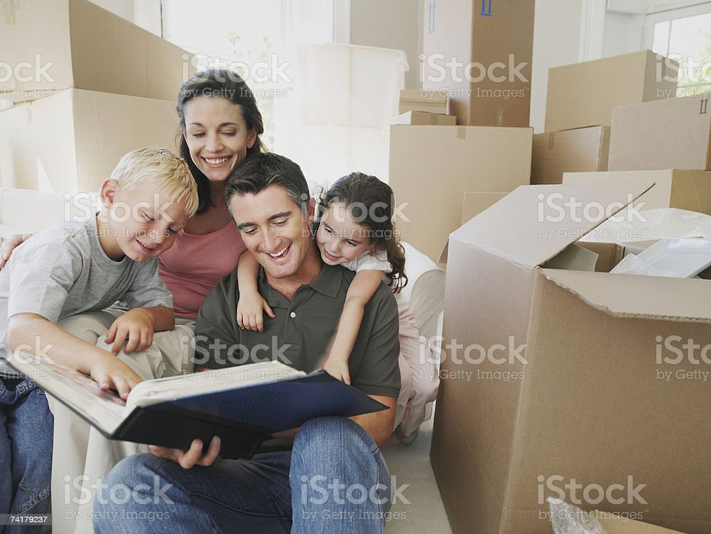 Man and woman with boy and girl looking at photo album in house with cardboard boxes royalty-free stock photo
