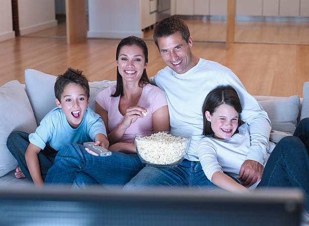 Man and woman with boy and girl watching television and eating popcorn stock photo