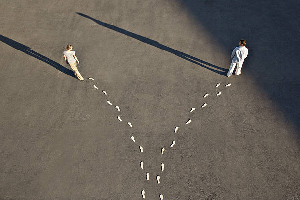 Man and woman with diverging line of footprints stock photo