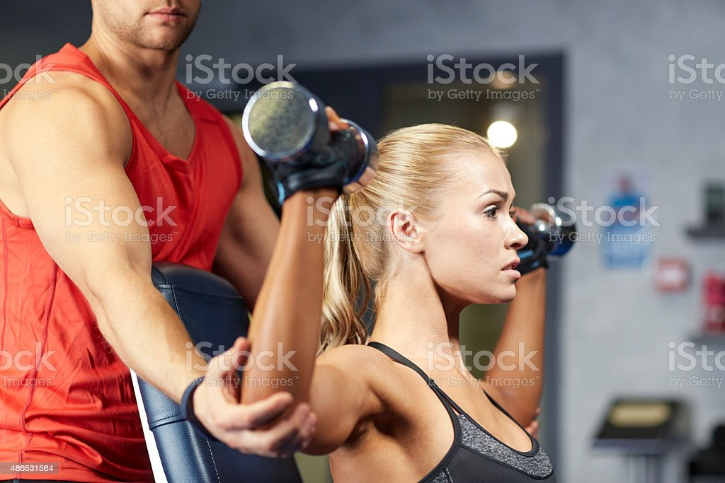 man and woman with dumbbells in gym stock photo