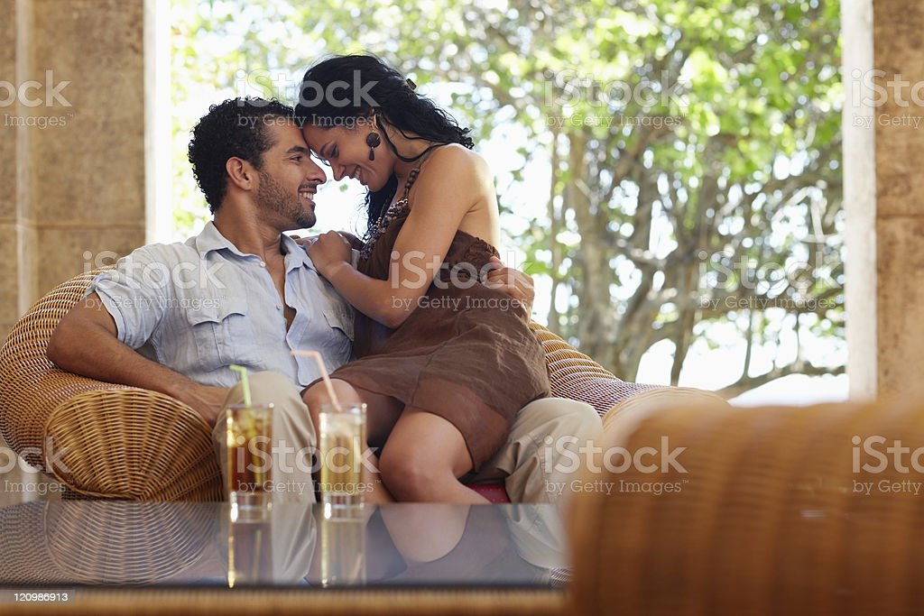 Man and woman with foreheads touching, with drinks on table royalty-free stock photo