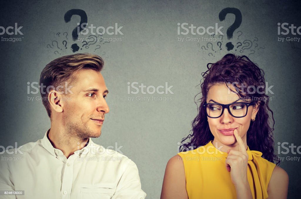 Man and woman with question mark looking at each other with interest stock photo
