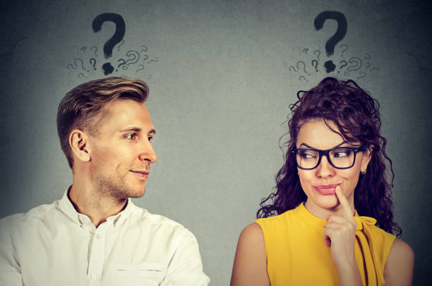 Man and woman with question mark looking at each other with interest Man and woman with question mark looking at each other with interest romantic activity stock pictures, royalty-free photos & images