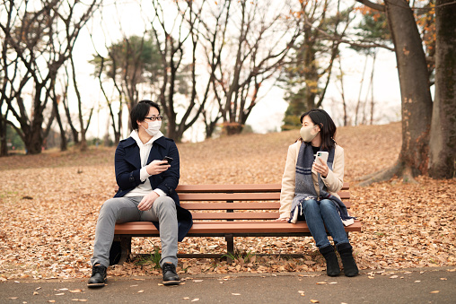 Man and woman with smart phone talking in keeping social distance