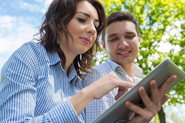 mann und frau mit tablet pc auf blauer himmel hintergrund - natürliche make up kurse stock-fotos und bilder