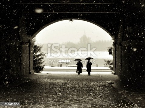 Man and woman with umbrellas under bridge in snow day Dresden Elbe water front