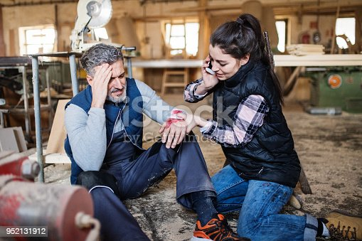 istock Man and woman workers after an accident in the carpentry workshop. 952131912