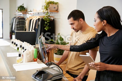 istock Man and woman working behind the counter in a clothing store 901863898