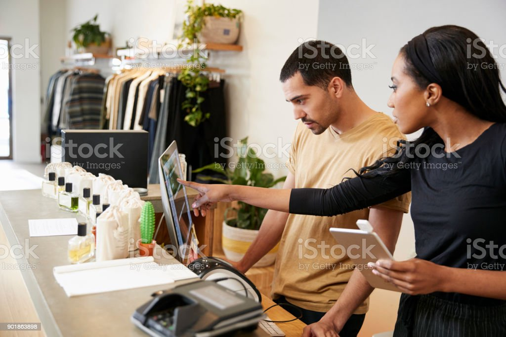 Man and woman working behind the counter in a clothing store stock photo