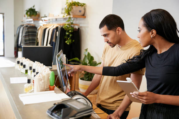 man and woman working behind the counter in a clothing store - shopping stock photos and pictures