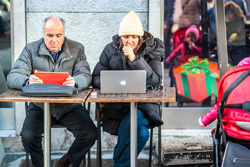 Man and woman working in outdoor cafe, Milan