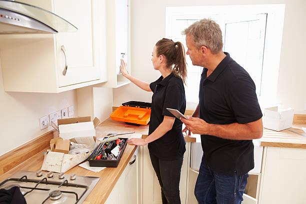 man and woman working on a new kitchen installation - looking inside inside cabinet bildbanksfoton och bilder