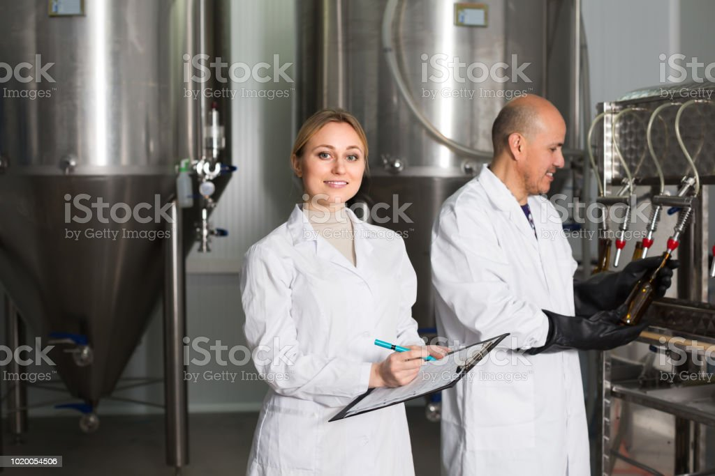 Man and woman working on brewery stock photo
