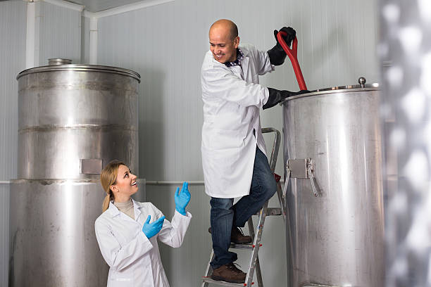Man and woman working on modern brewery stock photo