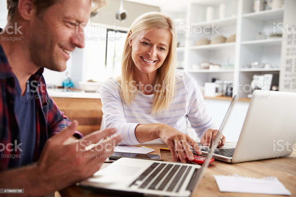 Man and woman working together at home stock photo